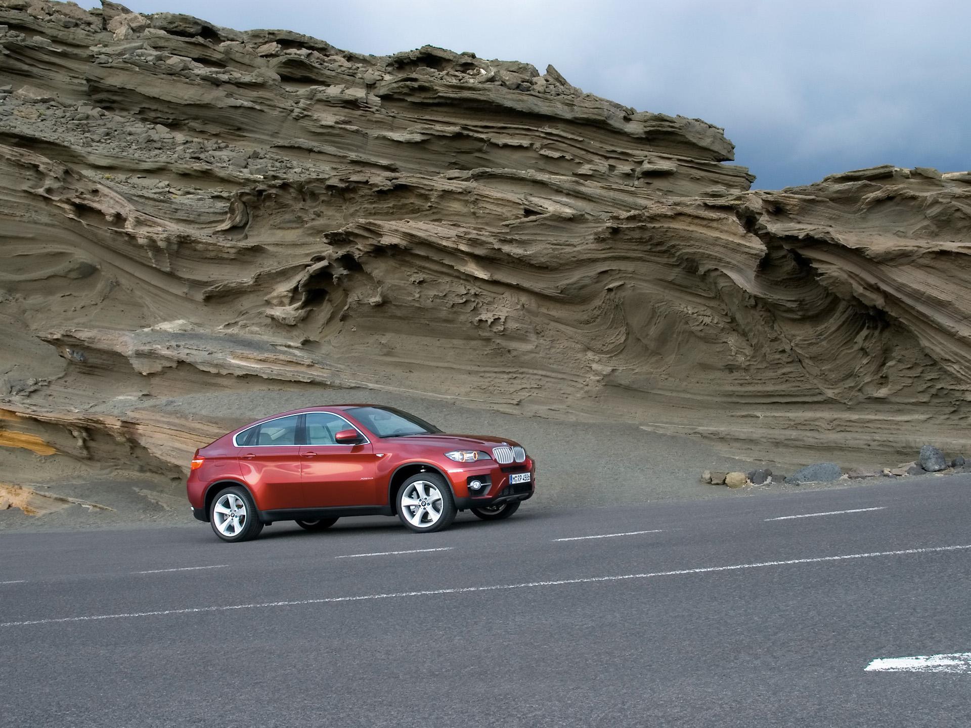 Vue de 3/4 avant de la BMX X6 xDrive50i.<br> La ligne de toit est typique d'un coupé, et donne de l'élégance à cette BMX X6 xDrive50i qui apparaît sportive et musculeuse. La forme étirée des surfaces vitrées latérales participe à la fluidité de la silhouette, inédite sur un SUV, justifiant le terme de Sports Activity Coupe pour qualifier cette BMX X6 xDrive50i.